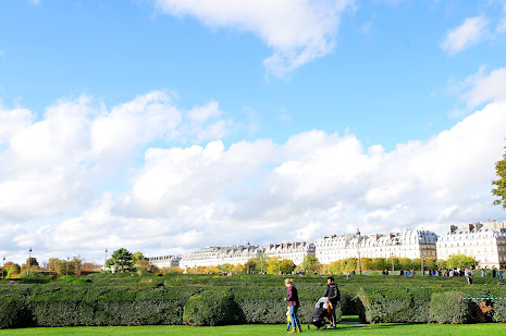 wide angle photo of sky & garden & a couple with kid in Paris