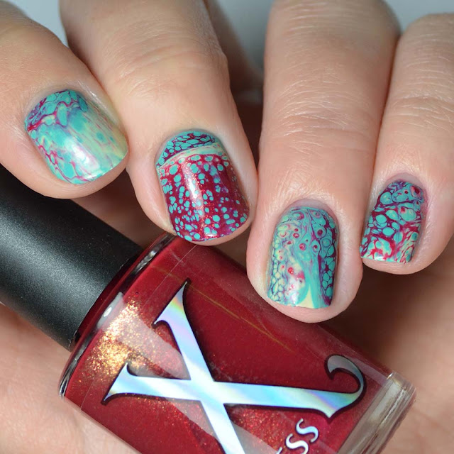 red fluid art polish with gold shimmer nail art