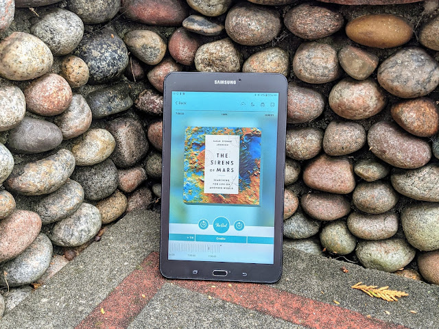 """Tablet displaying the Libby audiobook page for """"The Sirens of Mars"""" on a concrete bench with stone surround"""