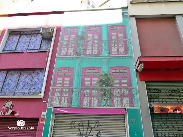 Vista ampla de um curioso e criativo grafite pintado na fachada de uma loja da Ladeira Porto Geral