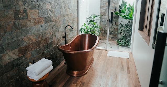 Freestanding copper bathtub in a rustic bathroom.
