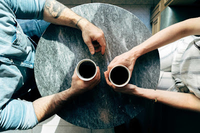Man and woman sitting opposite each other holding cups on table