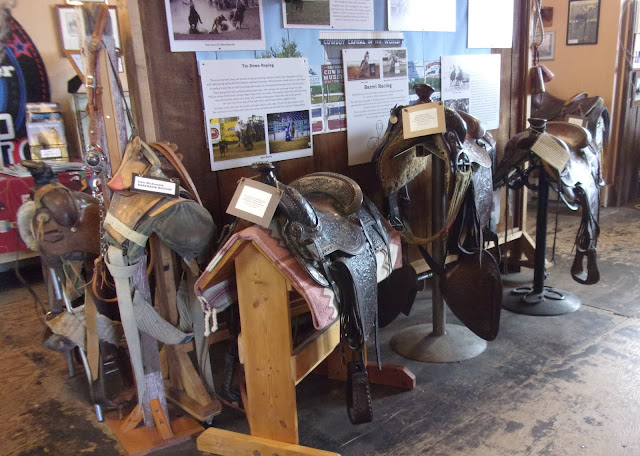 Saddles in the Oakdale Cowboy Museum.  Pictures and stories of past residents of the town are displayed on the wall