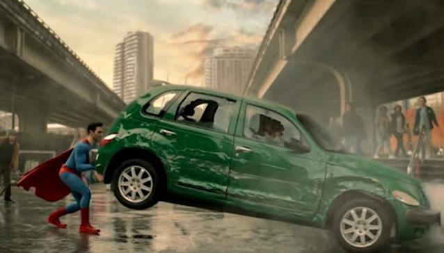 Cena do seriado em homenagem a dos quadrinhos: o Superman colocando um carro verde amassado no chão enquanto pessoas observam.