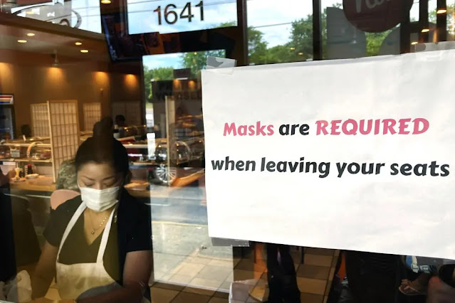 A sign asking to wear a mask in front of a restaurant in the US. Photo: AP