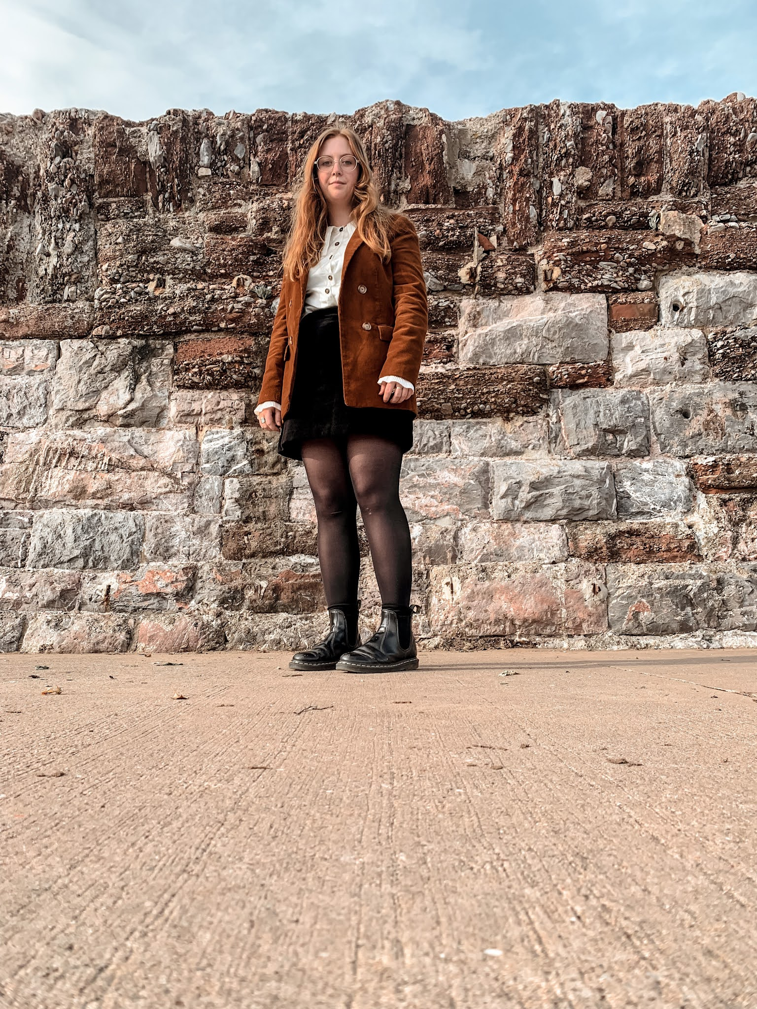 A woman with ginger hair and glasses standing in front of a brick wall. She is wearing a rust colour cord blazer, a cream silky shirt and black velvet skirt with black tights and black dr martens chelsea boots