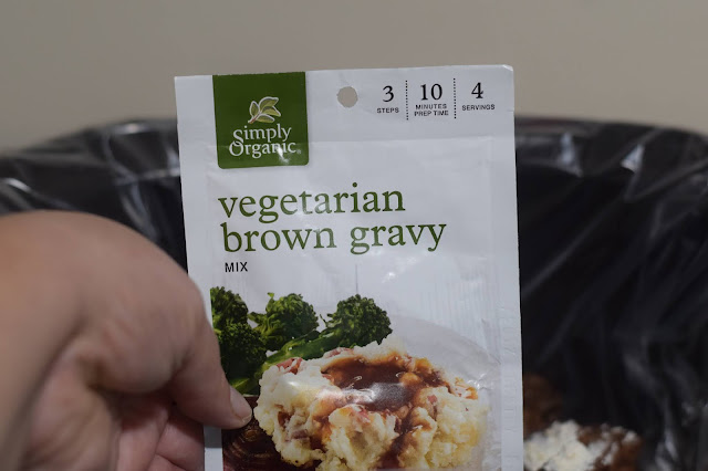 A packet of vegetarian brown gravy mix going into the crock pot.
