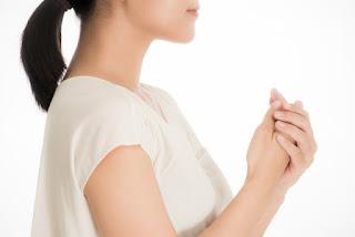 体が冷えて寒いので手をこすっている女性の写真