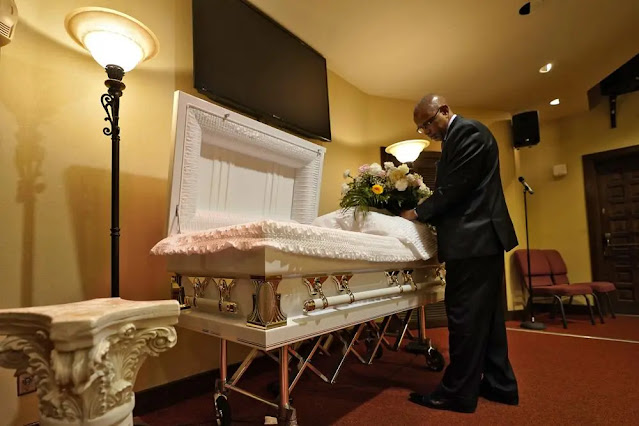 The director of a funeral home arranges flowers on a coffin before a ceremony in Tampa, Florida, USA. Photo: AP