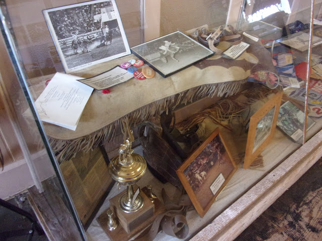 Pictures of past rodeo participants are displayed in a glass case