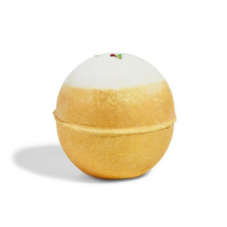 A spherical golden bath bomb with a hexagonal bottom with lush engraved into it coated in gold lustre with an engraved red and green holly on top on a bright background