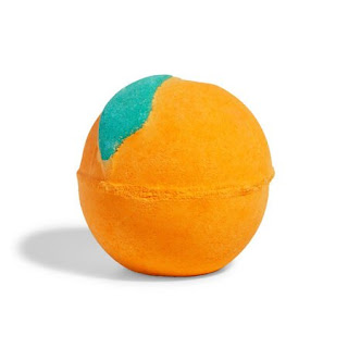 A spherical orange bath bomb with a leaf engraved into it on a white background