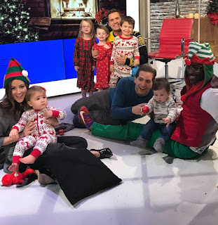 Picture of Peter Schrager playing with a child along with his co-host